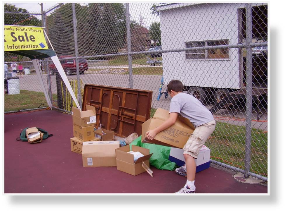Stacking the unloaded boxes of books on the tennis court in the Library booth's designated area.