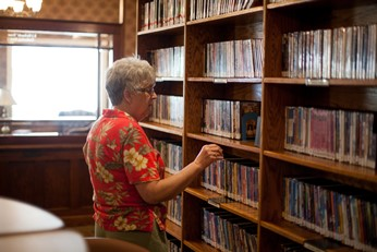 Shows a patron browsing the library's shelves